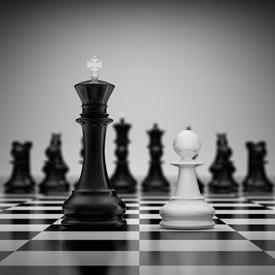 Tabuleiro de xadrez, em primeiro plano o rei preto frente a um peão branco. Em segundo plano as outras peças pretas